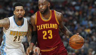 Cleveland Cavaliers forward LeBron James, right, drives the lane past Denver Nuggets forward Wilson Chandler in the first half of an NBA basketball game Wednesday, March 22, 2017, in Denver. (AP Photo/David Zalubowski)