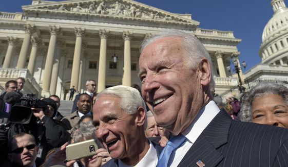 Former Vice President Joe Biden, right, and Rep. Charlie Crist, D-Fla., left, greet the crowd on Capitol Hill in Washington, Wednesday, March 22, 2017. Biden is on Capitol Hill to defend former President Barack Obama's Affordable Care Act. (AP Photo/Susan Walsh)