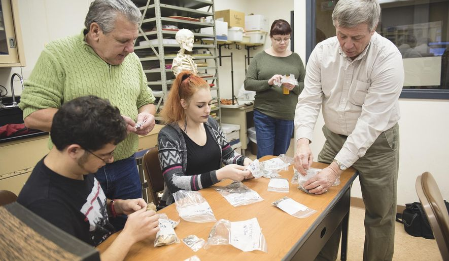 In this March 6, 2017 photo, Andrew Malhotra, Ivy Savidge, and Dwayne Santella students in the forensic anthropology course look through artifacts found from an excavation site as Dr. Cassandra Kuba and Dr. John P. Nass explain the materials, in California, Pa. (Thalia Juarez/Herald-Standard via AP)