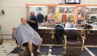 David Morris, right, owner of the King Barber Shop in downtown Kingsville, Texas, cuts Chuck Ludlam's hair at the shop on Thursday, March 9, 2017.  Morris moved to the location a year ago for better walk-in clientele. The city of Kingsville, in partnership with the UTSA is embarking on $2.4 million of improvements downtown. (Rachel Denny Clow/Corpus Christi Caller-Times via AP)