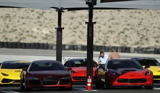 In this March 21, 2017, photo, people look at cars at SpeedVegas, Tuesday, March 21, 2017, in Las Vegas. An employee driving instructor is balking at signing a document declaring the tourist-oriented exotic auto racing track is safe, and is asking a state court judge to close the track and order a redesign. Two people were killed in a crash at the track in February. (AP Photo/John Locher)