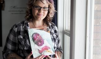 Amanda Harris holds a picture of her son Michael as she poses for a portrait Thursday, Feb. 2, 2017, at her parent's home in Burley, Idaho. Michael was born premature and died shortly after Harris gave birth. 'You'll never get over it, but you can recover,' she says. (Pat Sutphin/The Times-News via AP)