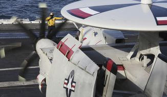 In this Monday, March 20, 2017 photograph, crew reposition an E-2C Hawkeye on the USS George H.W. Bush as it travels toward the Strait of Hormuz. The arrival of the nuclear-powered aircraft carrier to the Persian Gulf marks the first such deployment under new U.S. President Donald Trump. (AP Photo/Jon Gambrell)