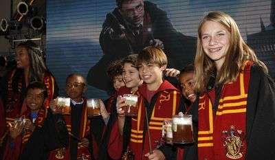 FILE - In this Dec. 6, 2011. file photo, fans dress up as students from Hogwarts School of Witchcraft and Wizardry make a butterbeer toast as Universal Parks & Resorts announces the Harry Potter attraction is coming to Universal Studios Hollywood in Universal City, Calif. Pennsylvania's Yuengling's Ice Cream launched a butterbeer flavored ice cream on March 20, 2017. (AP Photo/Jason Redmond, File)