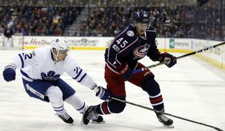 Toronto Maple Leafs defenseman Nikita Zaitsev, left, of Russia, knocks the puck away from Columbus Blue Jackets forward Lukas Sedlak, of the Czech Republic, during the second period of an NHL hockey game in Columbus, Ohio, Wednesday, March 22, 2017. (AP Photo/Paul Vernon)