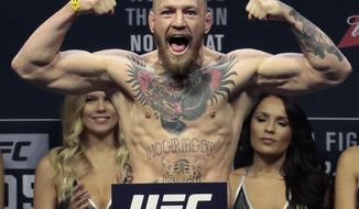 FILE - In this Friday, Nov. 11, 2016, file photo, Conor McGregor stands on a scale during the weigh-in event for his fight against Eddie Alvarez in UFC 205 mixed martial arts at Madison Square Garden in New York. Nevada athletic officials have significantly reduced the penalty they imposed on UFC star Conor McGregor following a profanity-laced, bottle-throwing fracas with a rival during a pre-fight news conference in Las Vegas. The Nevada Athletic Commission on Wednesday, March 22, 2017, approved an agreement with McGregor that settled the disciplinary action with a $25,000 fine, 25 hours of community service and the state's legal costs. (AP Photo/Julio Cortez, File)
