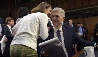 Marie Louise Gorsuch, wife of Supreme Court Justice nominee Neil Gorsuch, talks to her husband during a break in testimony on Capitol Hill in Washington, Wednesday, March 22, 2017, during his confirmation hearing before the Senate Judiciary Committee. (AP Photo/Susan Walsh)