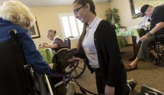 In this Tuesday, March 7, 2017 photo, resident Irma Porter pets Lucy as she and her owner Alexandra Burnham visit residents at the Beehive Homes in Farmington, N.M. (Jon Austria /The Daily Times via AP)