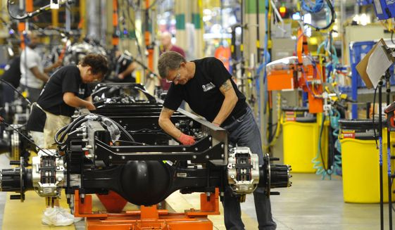 In this photo taken Aug. 12, 2015, workers assemble a truck at Ford Motor Company's Ohio Assembly Plant Wednesday, Aug. 12, in Avon Lake, Ohio. The United Auto Workers union on Friday, Nob. 6, 2015, has reached a tentative contract agreement with Ford. The contract covers 53,000 workers at 22 U.S. plants.  (AP Photo/David Richard)