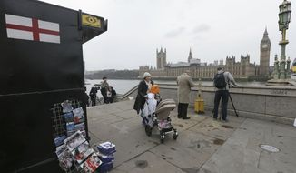 "People walk past a souvenir stall on Westminster Bridge after it was re-opened to the public Thursday, March 23, 2017, following an attack on Wednesday when a man drove a car into pedestrians then stabbed a police officer to death before being fatally shot by police within Parliament's grounds. The IS-linked Aamaq news agency said Thursday that the person who carried out the ""attack in front of the British parliament in London was a soldier of the Islamic State."" (AP Photo/Tim Ireland)"