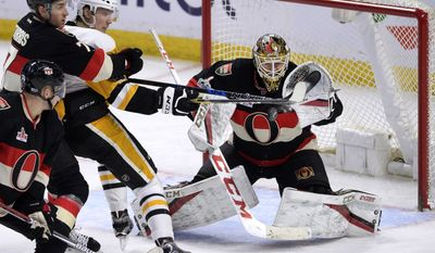Ottawa Senators goalie Mike Condon (1) reaches for the puck as Kyle Turris (7) wraps up Pittsburgh Penguins' Oskar Sundqvist (40) during the third period of an NHL hockey game in Ottawa, Ontario, Thursday, March 23, 2017. Ottawa won, 2-1. (Justin Tang/The Canadian Press via AP)