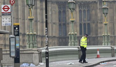 A police officer stands on Westminster Bridge with the Houses of Parliament in background, in London, Thursday March 23, 2017. On Wednesday a knife-wielding man went on a deadly rampage, first driving a car into pedestrians on Westminster Bridge then stabbing a police officer to death before being fatally shot by police within Parliament's grounds in London. (AP Photo/Tim Ireland)