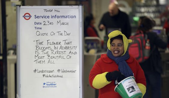 A woman collecting money for charity stands next to a quote written on an information board at Tower Hill underground train station, written in defiance of the previous day's attack in London, Thursday, in this March 23, 2017, file photo. On Wednesday, a man went on a deadly rampage, first driving a car into pedestrians then stabbing a police officer to death before being fatally shot by police within Parliament's grounds in London. (AP Photo/Matt Dunham) ** FILE **
