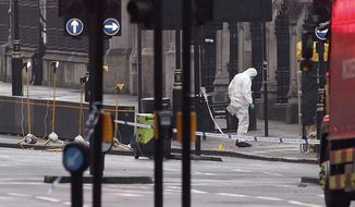 A forensic officer works near the Houses of Parliament in London, Britain, the day after a terrorist attack, Thursday March 23, 2017. A knife-wielding man went on a deadly rampage in the heart of Britain's seat of power Wednesday, plowing a car into pedestrians on London's Westminster Bridge before stabbing a police officer to death inside the gates of Parliament. Five people were killed, including the assailant. (Jonathan Brady/PA via AP)