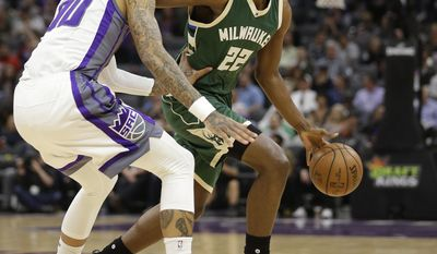 Sacramento Kings center Willie Cauley-Stein, left, guards Milwaukee Bucks guard Khris Middleton during the first half of an NBA basketball game, Wednesday, March 22, 2017, in Sacramento, Calif. (AP Photo/Rich Pedroncelli)