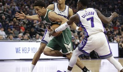Milwaukee Bucks guard Malcolm Brogdon, left, drives between Sacramento Kings' Skal Labissiere, back, and Darren Collison during the first half of an NBA basketball game, Wednesday, March 22, 2017, in Sacramento, Calif.(AP Photo/Rich Pedroncelli)