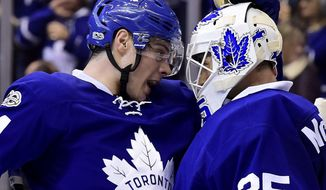 Toronto Maple Leafs centre Auston Matthews (34) and Toronto Maple Leafs goalie Curtis McElhinney (35) celebrate the Leafs' win following the third period of an NHL hockey game in Toronto on Thursday, March 23, 2017. (Frank Gunn/The Canadian Press via AP)