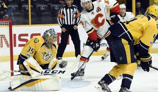 Nashville Predators goalie Pekka Rinne (35), of Finland, stops a shot as Calgary Flames right wing Troy Brouwer (36) looks for the rebound during the first period of an NHL hockey game Thursday, March 23, 2017, in Nashville, Tenn. (AP Photo/Mark Zaleski)
