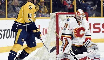 Calgary Flames goalie Chad Johnson (31) blocks a shot as Nashville Predators center Colton Sissons (10) looks for the rebound during second period of an NHL hockey game Thursday, March 23, 2017, in Nashville, Tenn. (AP Photo/Mark Zaleski)