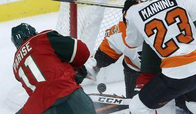 Minnesota Wild's Zach Parise, left, scores a goal on Philadelphia Flyers goalie Steve Mason, past Flyers defender Brandon Manning, right, during the first period of an NHL hockey game Thursday, March 23, 2017, in St. Paul, Minn. (AP Photo/Jim Mone)
