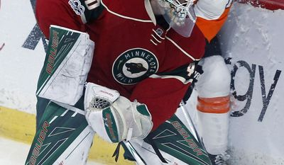 Philadelphia Flyers' Sean Couturier, right, tries to maneuver between Minnesota Wild goalie Devan Dubnyk and the boards during the first period of an NHL hockey game Thursday, March 23, 2017, in St. Paul, Minn. (AP Photo/Jim Mone)