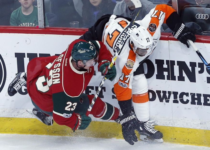 Minnesota Wild's Gustav Olofsson, left, of Sweden, races for the puck with Philadelphia Flyers' Wayne Simmonds during the first period of an NHL hockey game Thursday, March 23, 2017, in St. Paul, Minn. (AP Photo/Jim Mone)