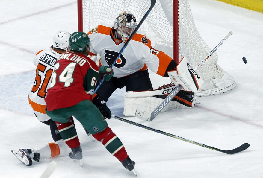 Philadelphia Flyers goalie Steve Mason, right, deflects a shot by Minnesota Wild's Mikael Granlund during the second period of an NHL hockey game Thursday, March 23, 2017, in St. Paul, Minn. (AP Photo/Jim Mone)