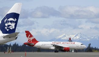 FILE - In this Monday, April 4, 2016, file photo, a Virgin America plane taxis past an Alaska Airlines plane waiting at a gate, at Seattle-Tacoma International Airport in Seattle. Alaska said Wednesday, March 22, 2017, that it will retire the Virgin brand, probably in 2019. Alaska announced in 2016, that it was buying Virgin, but CEO Brad Tilden held out hope to Virgin fans that he might keep the Virgin America brand, and run it and Alaska as separate airlines under the same corporate umbrella. (AP Photo/Ted S. Warren, File)
