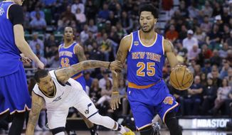 New York Knicks guard Derrick Rose (25) drives around Utah Jazz guard George Hill, left, during the first half during an NBA basketball game Wednesday, March 22, 2017, in Salt Lake City. (AP Photo/Rick Bowmer)