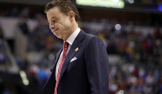 "FILE - In this Sunday, March 19, 2017, file photo, Louisville head coach Rick Pitino walks off the court after a 73-69 loss to Michigan in a second-round game in the men's NCAA college basketball tournament in Indianapolis. The NCAA is standing by its allegations against the Louisville men's basketball program and Pitino, saying the coach failed to notice ""red flags"" in activities by a former staffer who an escort says hired dancers for sex parties with recruits and players. (AP Photo/Jeff Roberson, File)"