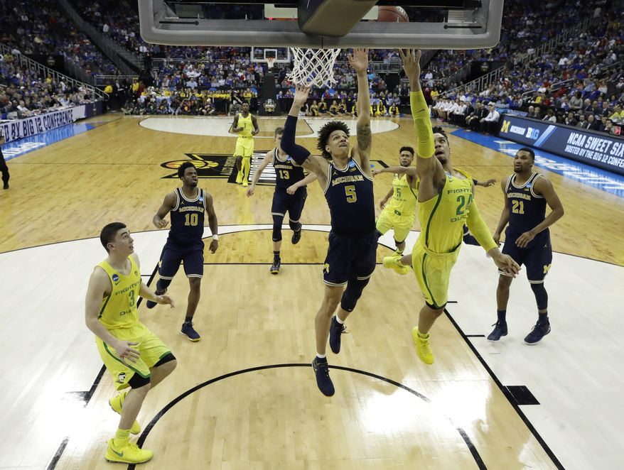 Oregon forward Dillon Brooks drives to the basket ahead of Michigan forward D.J. Wilson (5) during the second half of a regional semifinal of the NCAA men's college basketball tournament, Thursday, March 23, 2017, in Kansas City, Mo. (AP Photo/Charlie Riedel)