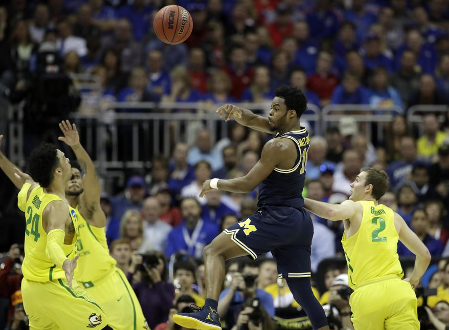 Michigan guard Derrick Walton Jr., center, passes between Oregon's Dillon Brooks, left, and Casey Benson, right, during the second half of a regional semifinal of the NCAA men's college basketball tournament, Thursday, March 23, 2017, in Kansas City, Mo. (AP Photo/Charlie Riedel)