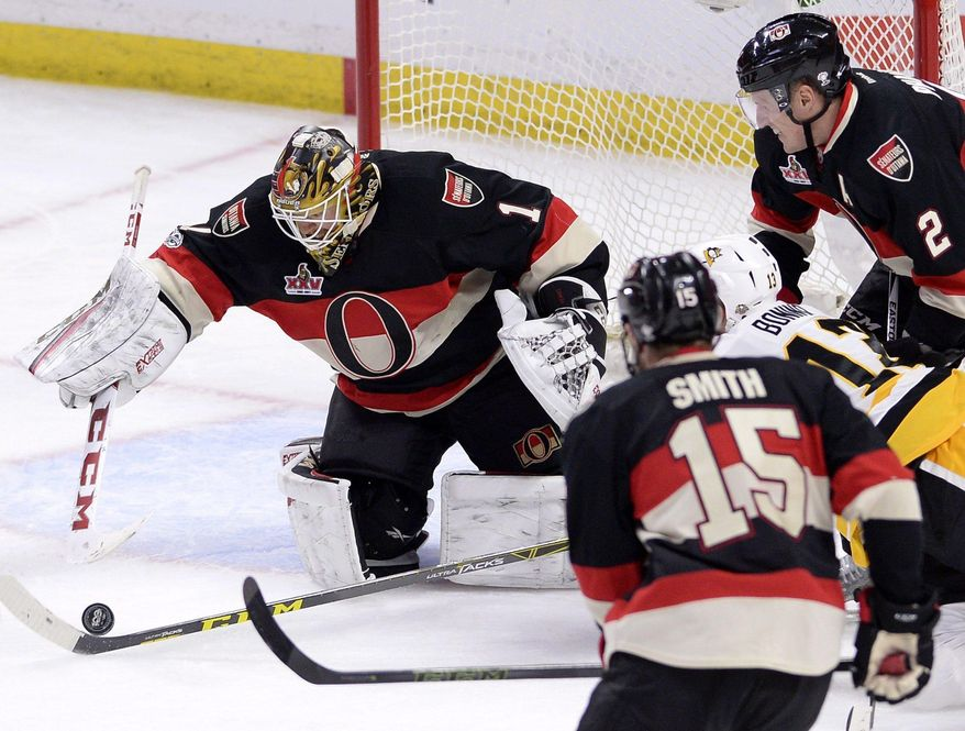 Ottawa Senators goalie Mike Condon (1) reaches for the puck against Pittsburgh Penguins' Nick Bonino (13) as Senators' Zack Smith (15) and Dion Phaneuf (2) look on during the third period of an NHL hockey game in Ottawa, Ontario, Thursday, March 23, 2017. Ottawa won, 2-1. (Justin Tang/The Canadian Press via AP)