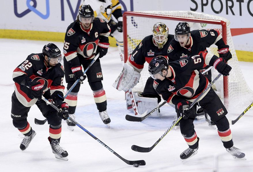 Ottawa Senators' Chris Kelly (22), Tommy Wingels (57), Erik Karlsson (65) and Chris Wideman (6) work to clear the puck away from goalie Mike Condon (1) during the third period of an NHL hockey game in Ottawa, Ontario, Thursday, March 23, 2017. Ottawa won, 2-1. (Justin Tang/The Canadian Press via AP)
