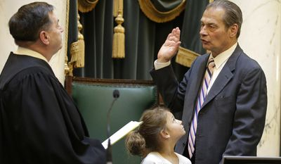 Sen. Dominick Ruggerio is sworn in as President of the Rhode Island Senate by former Senate President and Superior Court Judge Joseph Montalbano as Ruggerio's granddaughter Ava Ruggerio holds the bible at the Rhode Island Statehouse Thursday, March 23, 2017, in Providence, R.I. (AP Photo/Stephan Savoia)