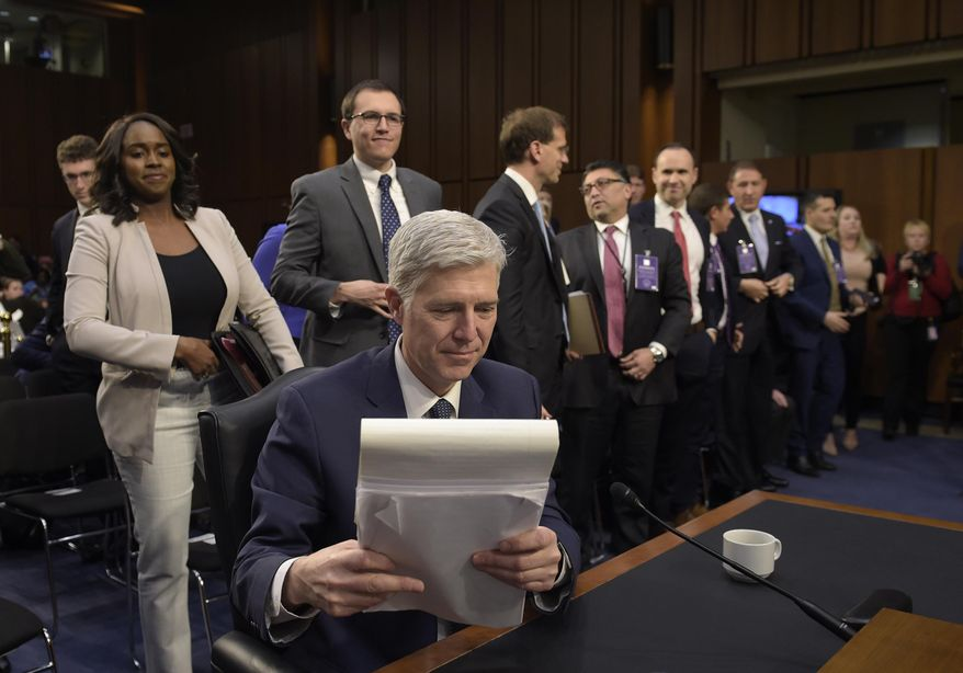 Supreme Court Justice nominee Neil Gorsuch gathers his papers on Capitol Hill in Washington on Wednesday, during a break in his confirmation hearing before the Senate Judiciary Committee. Judge Grouch's supporters say he is a kind, open-minded man. However, Grosuch's opponents have said Grosuch lacks empthy, pointing to his 2008 Individuals with Disabilities Education Act ruling. (AP Photo/Susan Walsh)