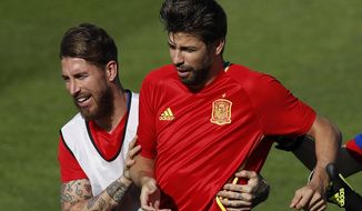 FILE - In this June 24, 2016 file photo, Spain's Sergio Ramos, left, grabs Gerard Pique during a training session at the Sports Complex Marcel Gaillard in Saint Martin de Re in France. Sergio Ramos and Gerard Pique, defenders from rival clubs Real Madrid and Barcelona are calling a truce and are at peace while with Spain's national team after exchanging blows through social media and television interviews recently. (AP Photo/Manu Fernandez, File)