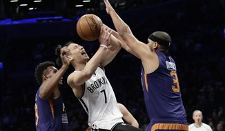 Brooklyn Nets' Jeremy Lin, center, drives between Phoenix Suns' Leandro Barbosa, left, and Jared Dudley during the first half of an NBA basketball game Thursday, March 23, 2017, in New York. (AP Photo/Frank Franklin II)