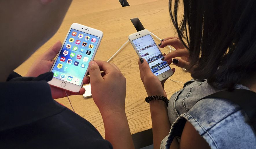 In this Saturday, June 18, 2016, file photo, customers try out Apple iPhone 6s models on display at an Apple Store in Beijing. (AP Photo/Mark Schiefelbein, File)