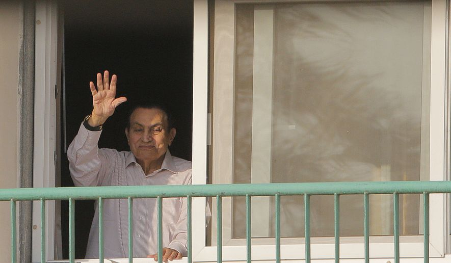In this Oct. 16, 2016 file photo, Ousted Egyptian President Hosni Mubarak waves to his supporters from his room at the Maadi Military Hospital as they celebrate the 43rd anniversary of the Oct. 6, 1973, war. An Egyptian security official said Friday, March 24, 2017, that Mubarak returned home after his release. (AP Photo/Amr Nabil, File)