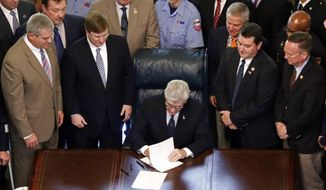 """Surrounded by lawmakers and law enforcement representatives, Gov. Phil Bryant, center, signs the """"Back The Badge Act of 2017"""" that would increase penalties for felonies or misdemeanors against law-enforcement officers, firefighters or emergency medical technicians that suspects committed """"with the specific intent to target an individual or group"""" because of their employment,"""" Friday, March 24, 2017 at the Capitol in Jackson, Miss. An overflow of law enforcement forced a relocation of the signing to the rotunda. (AP Photo/Rogelio V. Solis)"""