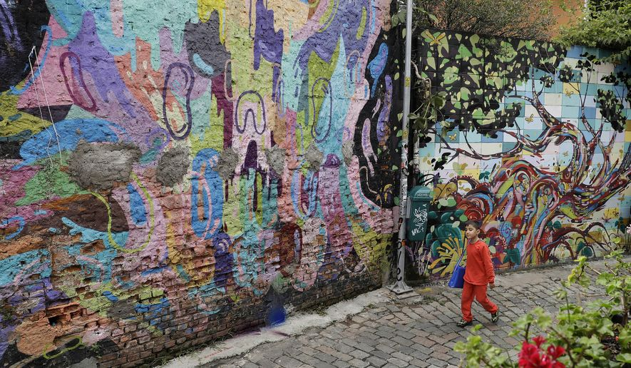 In this March 20, 2017 photo, a child walks alongside a street murals in Sao Paulo, Brazil. A campaign to clean up and beautify Sao Paulo has come under fire after the city's new mayor painted over a series of well-known graffiti murals. (AP Photo/Andre Penner)