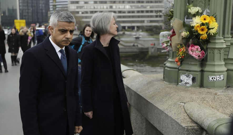 London Mayor Sadiq Khan stands on Westminster Bridge near floral tributes to victims of Wednesday's attack outside the Houses of Parliament in London, Friday March 24, 2017. (AP Photo/Matt Dunham)