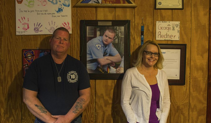 """George Redner Jr. and Jacqui Redner pose for a photo in front of a portrait of their son George """"Georgie"""" inside of their home in Levittown, Pa., on March 8, 2017. George committed suicide after suffering from PTSD from working in the Fire/EMS Service.  (Nate Smallwood/Pittsburgh Tribune-Review via AP)"""