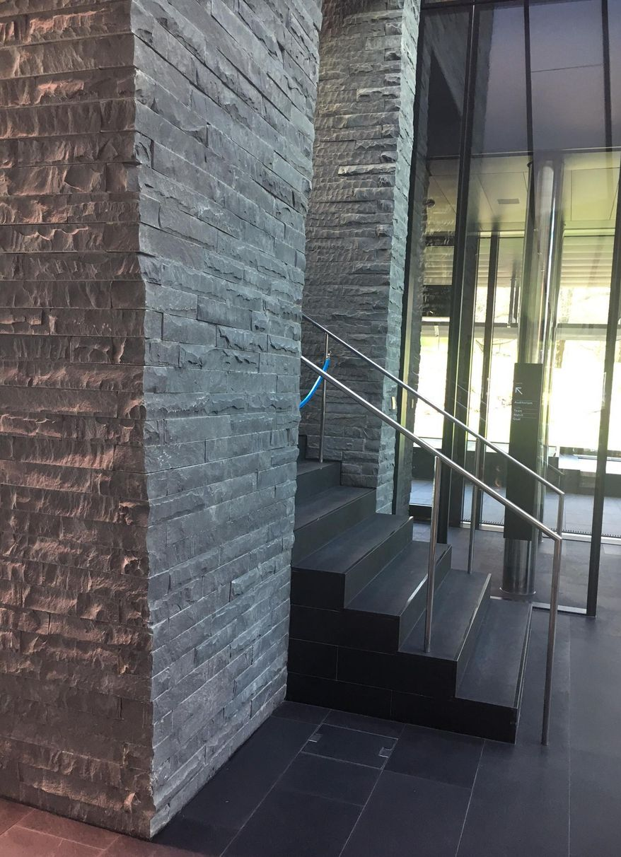 A plain slate wall in the reception of FIFA headquarters in Zurich, Thursday, March 23, 2017. FIFA has removed a monolithic reminder of former president Sepp Blatter from its headquarters. (AP Photo/Graham Dunbar)