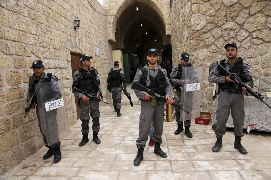 """In this Wednesday, March 22, 2017 photo, actors dressed as Israeli border policemen stand during a shoot of the """"Heaven's Gate"""" movie in a recreated alleyway of Jerusalem's Old City in Khan Younis, Gaza Strip. Surrounded by militant training sites on uprooted Jewish settlement lands, the first movie set in the Gaza Strip is growing, depicting the history-rich, volatile alleyways of Jerusalem's Old City.(AP Photo/Adel Hana)"""