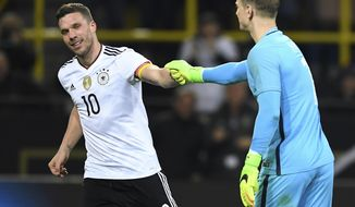 Germany's  Lukas Podolski is congratulated by England keeper  Joe Hart, right, during the friendly soccer match between Germany and England in Dortmund, Germany, Wednesday, March 22, 2017. (Marius Becker/dpa via AP)