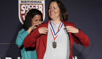 Shannon MacMillan, right, puts on a jacket with the help of teammate and friend Joy Fawcett during an induction ceremony for the National Soccer Hall of Fame Friday, March 24, 2017, in San Jose, Calif. (AP Photo/Marcio Jose Sanchez)