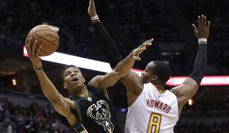 Milwaukee Bucks' Giannis Antetokounmpo shoots past Atlanta Hawks' Dwight Howard during the first half of an NBA basketball game Friday, March 24, 2017, in Milwaukee. (AP Photo/Morry Gash)