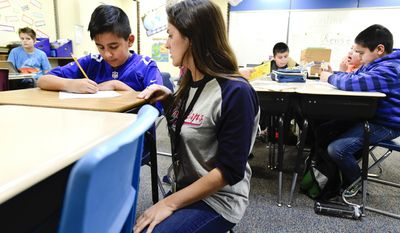 In this March 9, 2017 photo, Longmont Americorps  member Genevieve Spina works with fifth grader Yazir Trujillo after school at Rocky Mountain Elementary School in Longmont, Colo. (Matthew Jonas /The Daily Times Call via AP)